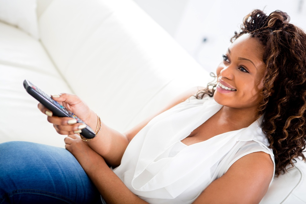 Woman watching television at home looking very happy.jpeg